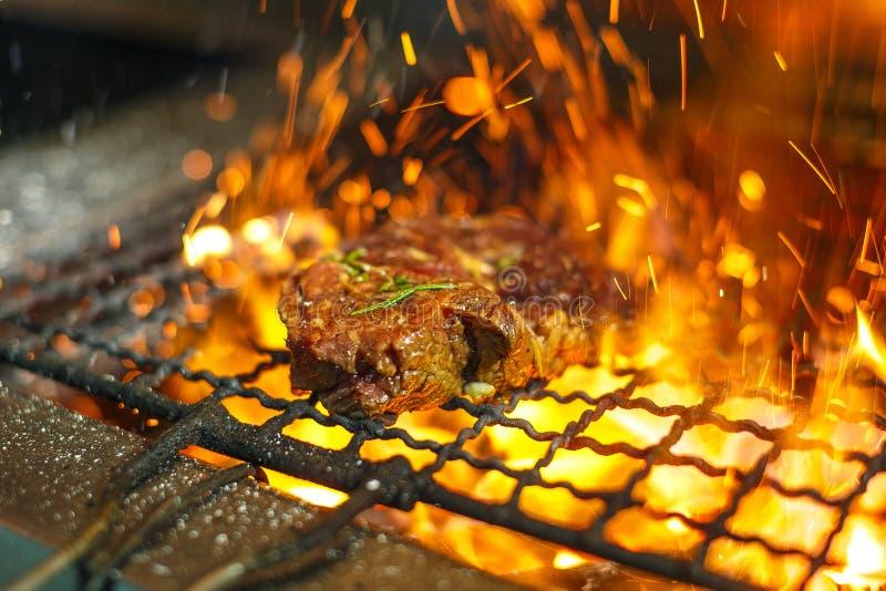 Filetes de carne de vaca en la parrilla con las llamas Carne asada a la parrilla en barbacoa con las llamas y los carbones Carne  fotos de archivo
