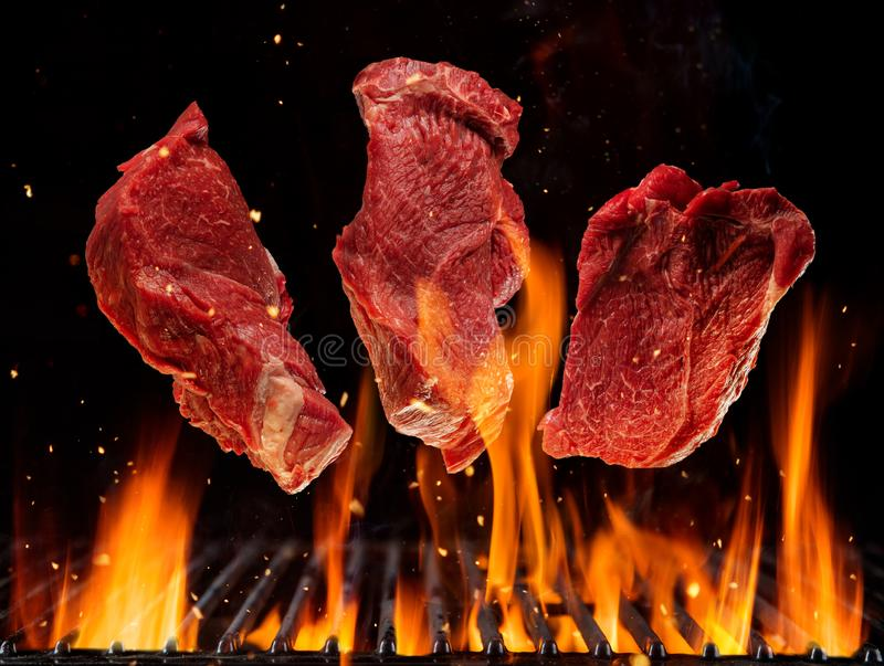 Filetes de carne de vaca crudos que vuelan sobre rejilla ardiendo de la parrilla stock de ilustración
