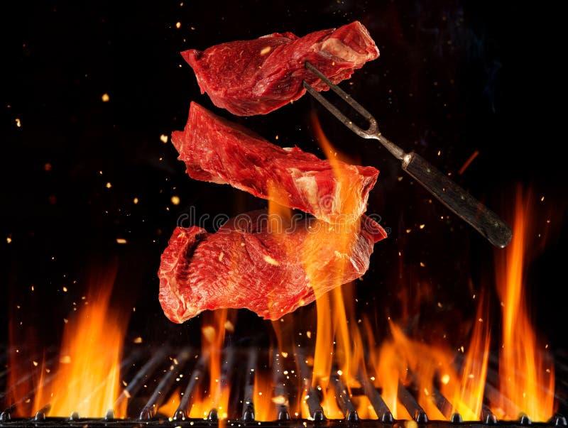 Filetes de carne de vaca crudos que vuelan sobre rejilla ardiendo de la parrilla ilustración del vector