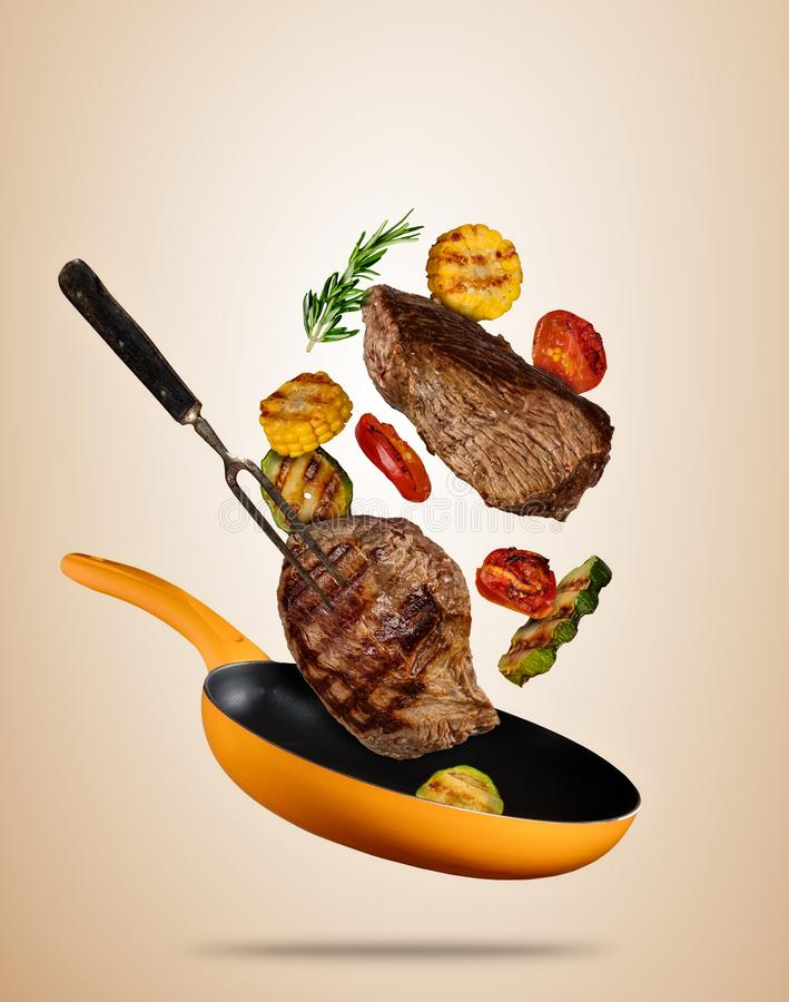 Filetes de carne de vaca del vuelo con la verdura asada a la parrilla en la cacerola, separada en b ilustración del vector