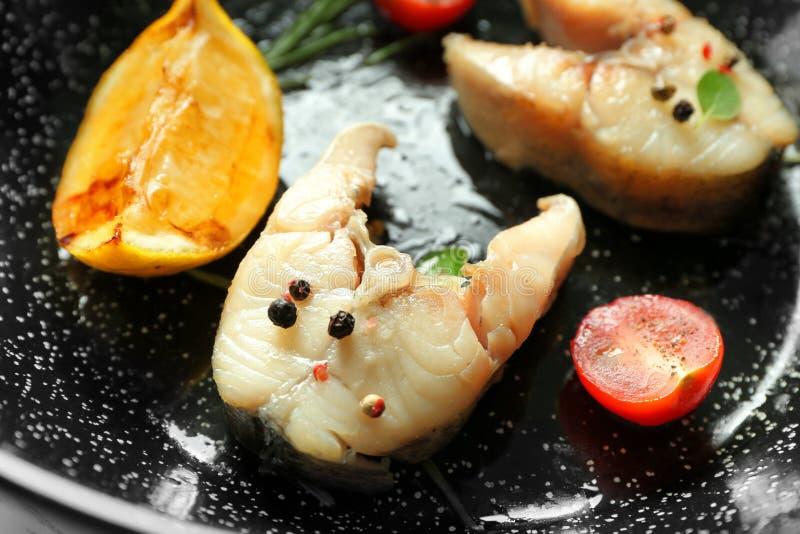 Filetes de pescados deliciosos en el sartén, primer fotografía de archivo
