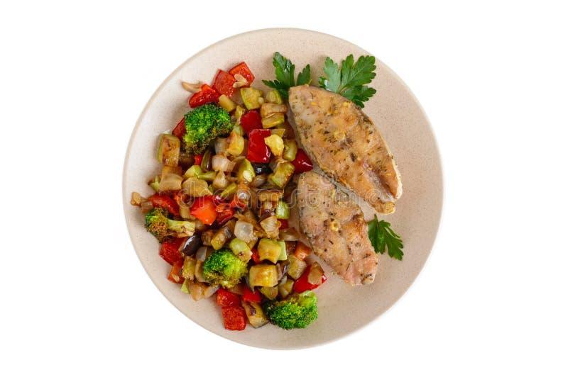 Filetes de pescados picantes fritos, servidos con una ensalada vegetal caliente en una placa de cerámica fotografía de archivo libre de regalías