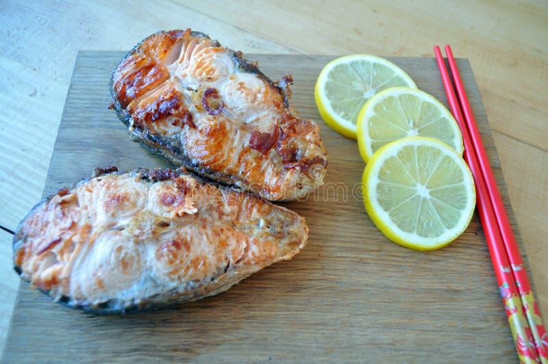 Filetes de pescados rojos con el limón y la salsa fotos de archivo