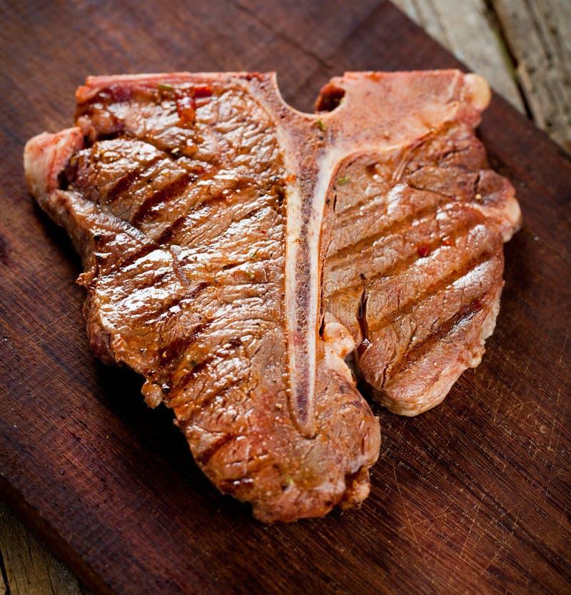 Filetes del T-hueso de la carne de vaca en el viejo tablero de madera oscuro foto de archivo