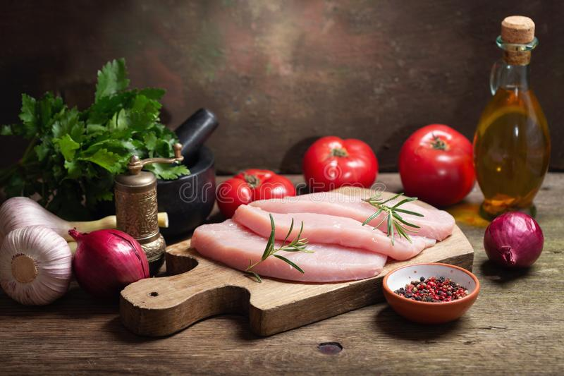 Filetes frescos de la carne del pavo con romero e ingredientes para cocinar foto de archivo libre de regalías