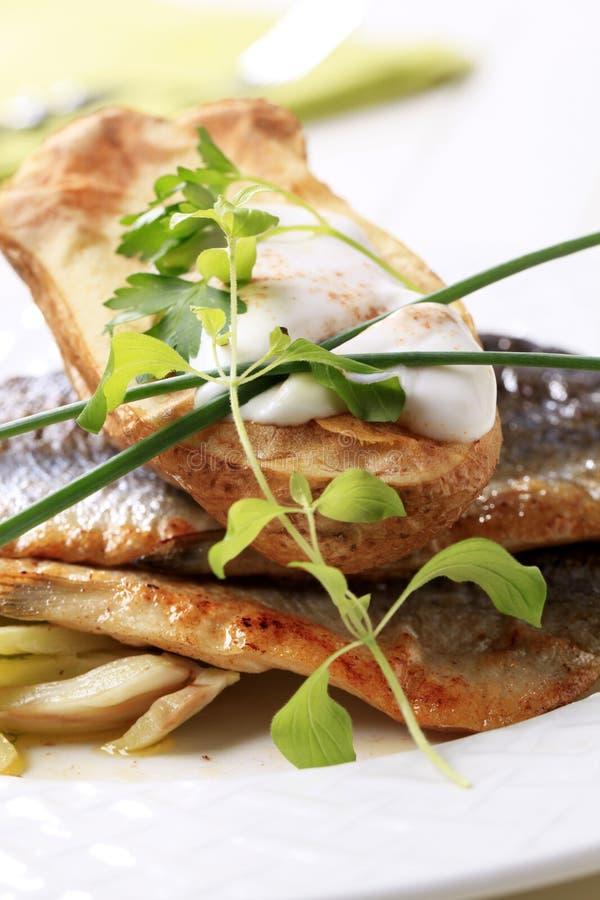 Filetes fritos cacerola de la trucha y patata cocida al horno imagen de archivo