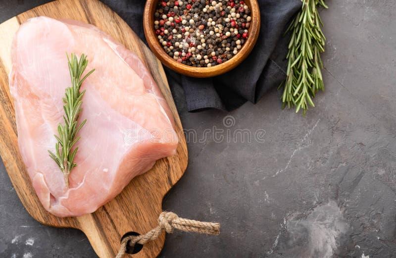 Filets crus de dinde sur la planche à découper noire avec des épices et des herbes Cuisson des ingrédients Concept sain naturel d photographie stock libre de droits