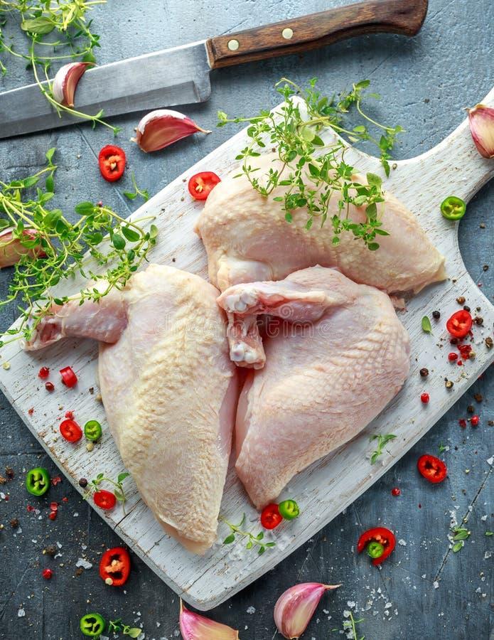 Filets crus de supremes de blanc de poulet avec des piments, des grains de poivre et le thym sur le hachoir en bois blanc images libres de droits