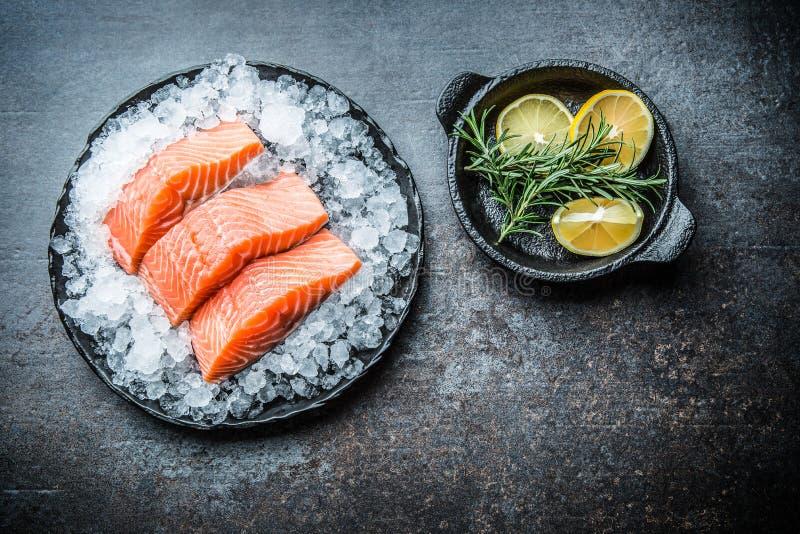 Filets saumonés crus dosés en glace de plat avec le citron et le romarin photographie stock libre de droits