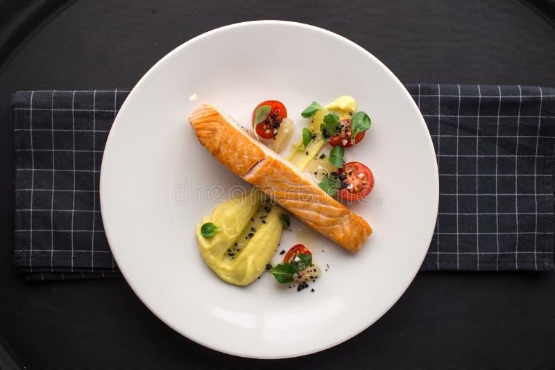 Filets saumonés grillés avec la mâche et les tomates de pomme de terre sur le conseil en pierre sur le fond noir images stock