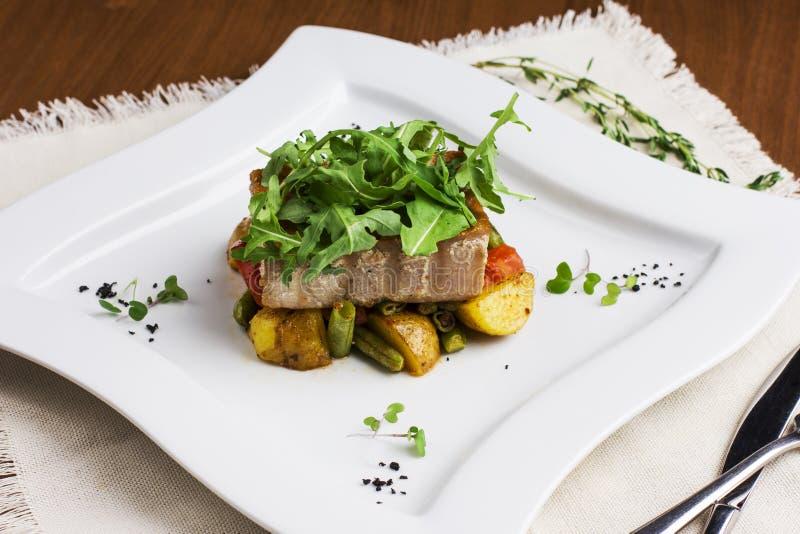 Filetti di pesce al forno con le patate ed i fagiolini sul pla del quadrato fotografia stock