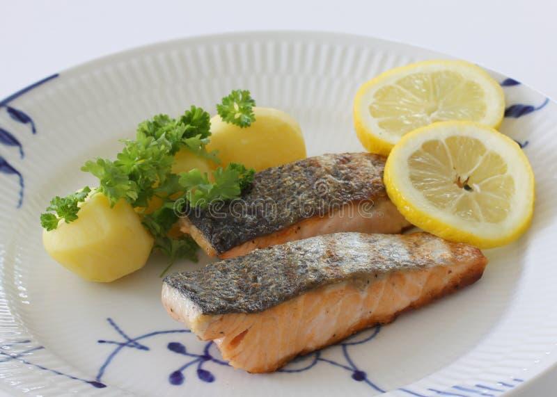 Filetti di pesce di color salmone arrostiti su un piatto con le patate, la trattativa e le fette di limone Fine sulla foto di ris fotografie stock