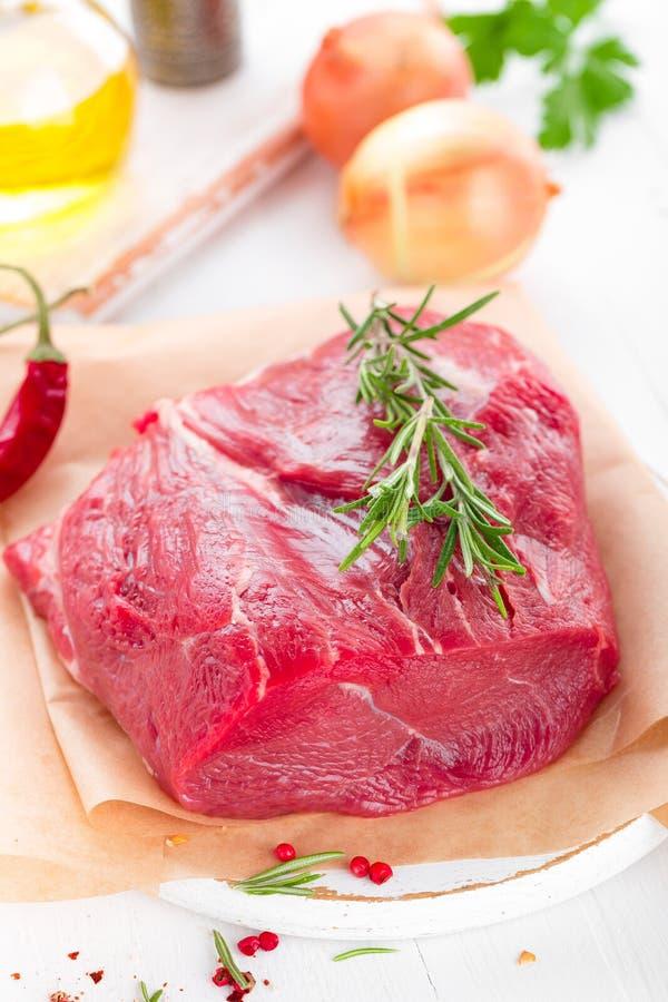 Filetto crudo della carne del manzo su fondo bianco con la cottura del primo piano degli ingredienti Carne fresca del manzo sul t immagine stock libera da diritti