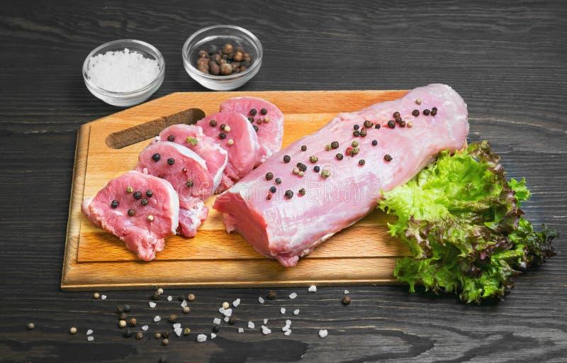 Filetto di carne di maiale della carne cruda sul tagliere fotografia stock