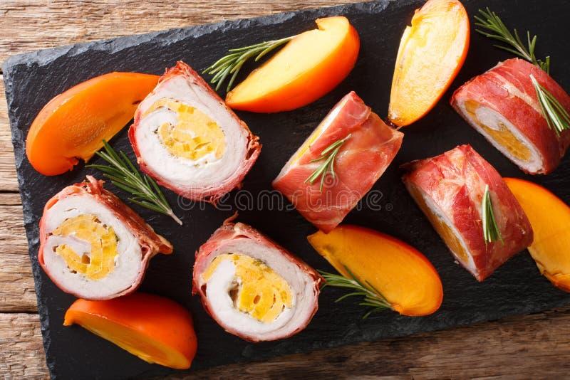 Filetto di carne di maiale delizioso farcito con il cachi e formaggio avvolto in primo piano di prosciutto di Parma vista superio immagine stock