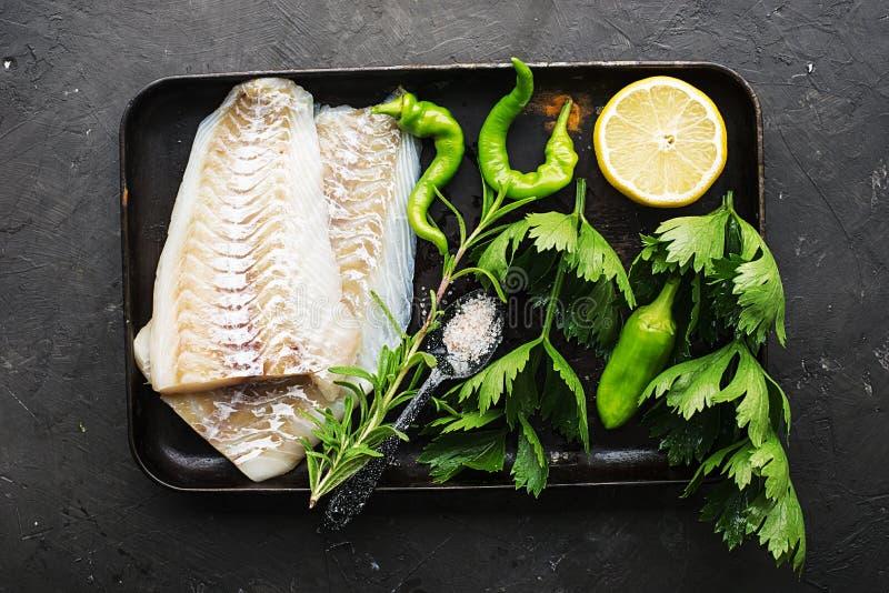 Filetto di merluzzo del pesce bianco fresco su un vassoio bollente con sedano, limone, erbe, peperone verde succoso Vista superio fotografie stock libere da diritti