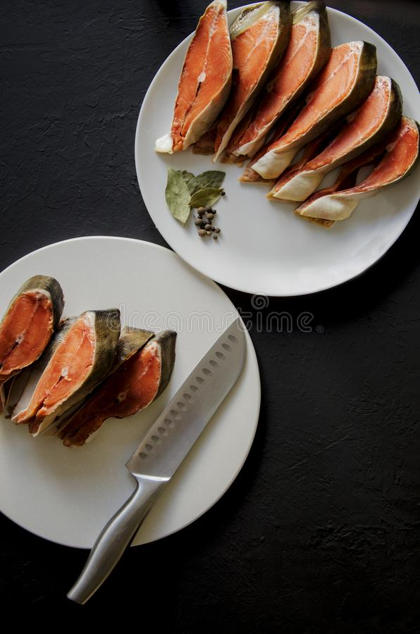 Filetto di pesce di color salmone crudo su fondo nero fotografie stock libere da diritti