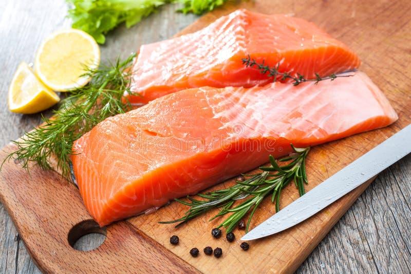 Filetto di pesce di color salmone crudo con le erbe fresche fotografia stock libera da diritti