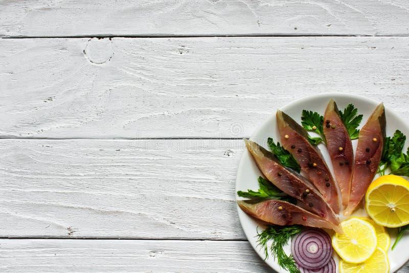 Filetto di pesce salato con le erbe, il limone e le spezie in un piatto immagine stock