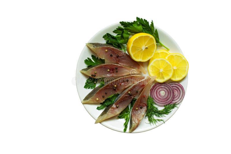 Filetto di pesce salato con le erbe, il limone e le spezie in un piatto immagine stock libera da diritti