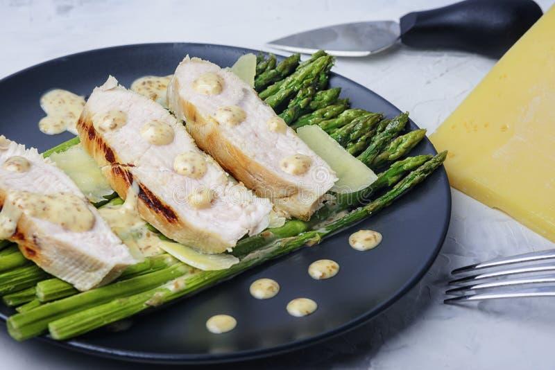 Filetto di tacchino tritato, asparagi verdi e formaggio parmigiano Un delizioso piatto dietetico con salsa di arachidi fotografia stock libera da diritti