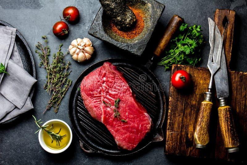 Filetto, erbe e spezie freschi di manzo della bistecca della carne cruda intorno al tagliere Alimento che cucina fondo con lo spa fotografia stock libera da diritti