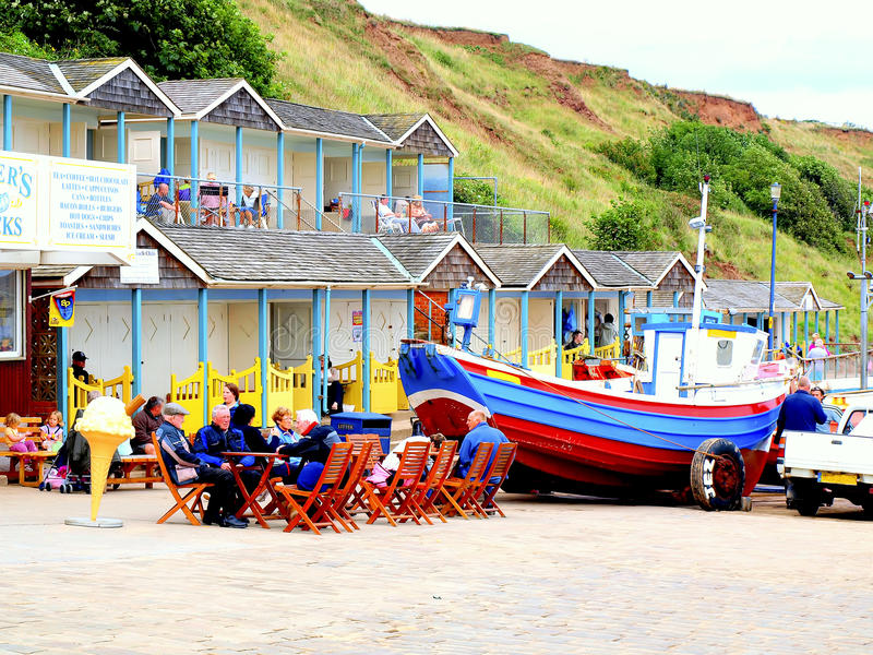 Filey, North Yorkshire. Alfresco cafe, beach chalets and a boat with wheels, on the promenade at Filey, North Yorkshire, England, UK stock image