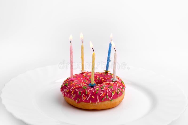 Filhós cor-de-rosa na placa branca como o bolo de aniversário com velas no fundo branco fotos de stock royalty free