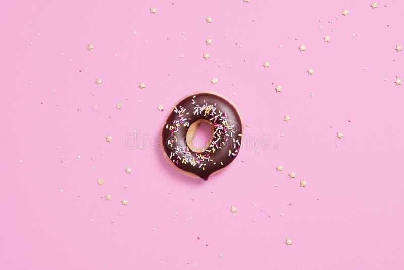A filhós do anel do chocolate com polvilha em um fundo do rosa pastel fotografia de stock royalty free