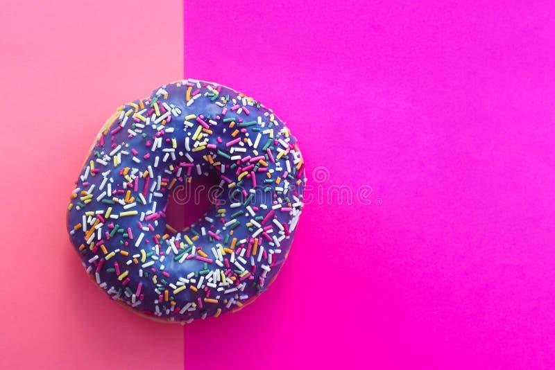 A filhós doce com crosta de gelo e colorida polvilha, em um fundo cor-de-rosa, a vista superior imagens de stock