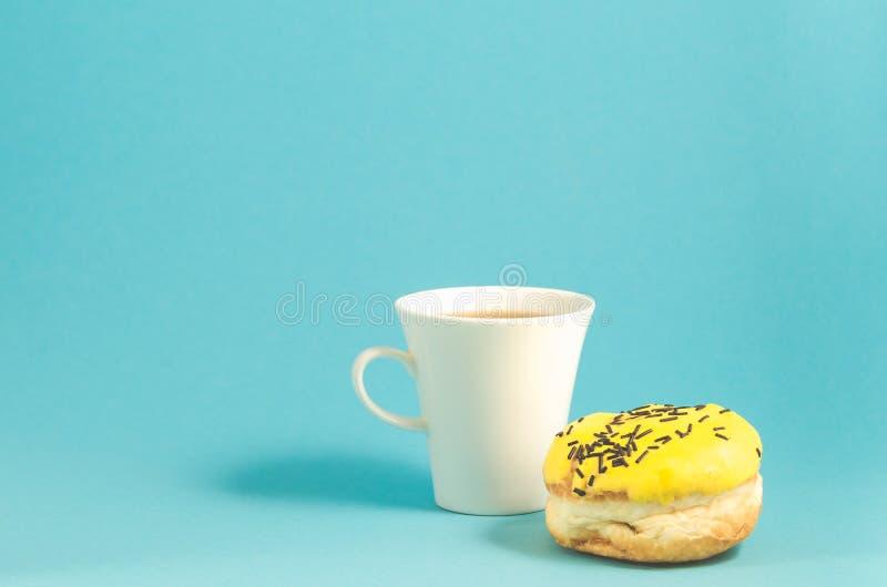 filhós e copo do coffe isolado no fundo azul /Donut no esmalte amarelo e copo branco do coffe no fundo azul Copie o espaço fotografia de stock royalty free