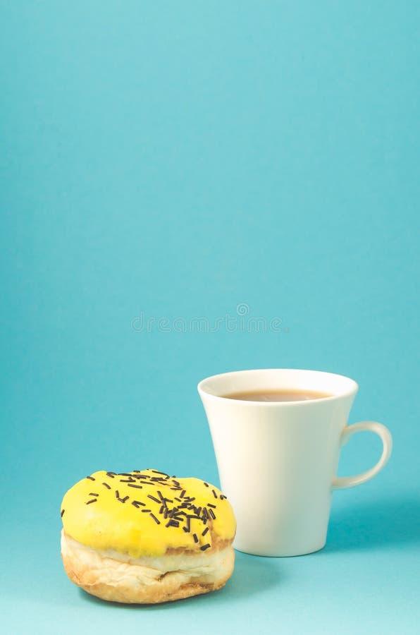 A filhós e o copo do coffe no fundo/filhós no esmalte amarelo decorado com as varas escuras do chocolate e no coffe azuis colocam imagens de stock
