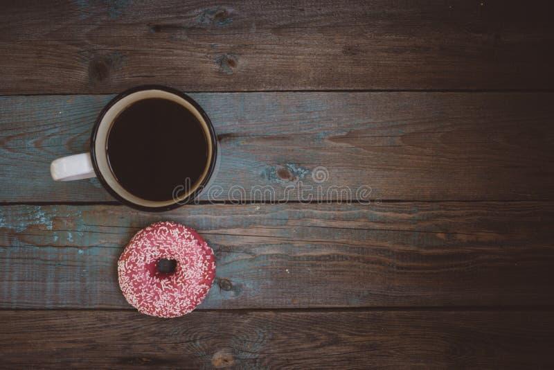 filhós fresca com a xícara de café na tabela de madeira imagem de stock