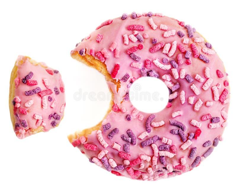 A filhós geada cor-de-rosa com colorido polvilha com uma mordida Filh?s da morango isolada no fundo branco Configura??o lisa Vist imagem de stock