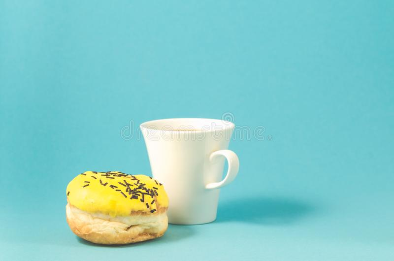 Filh?s no copo amarelo do esmalte e do coffe no fundo/filh?s azuis no esmalte amarelo e no copo branco do coffe no fundo azul com fotos de stock