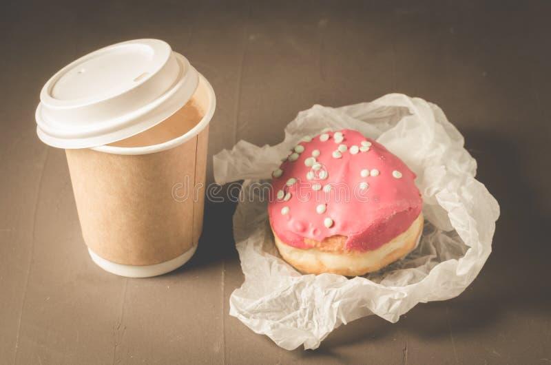 filhós no esmalte vermelho e um copo de café de papel/filhós no esmalte vermelho e um copo de café de papel em uma tabela escura fotografia de stock
