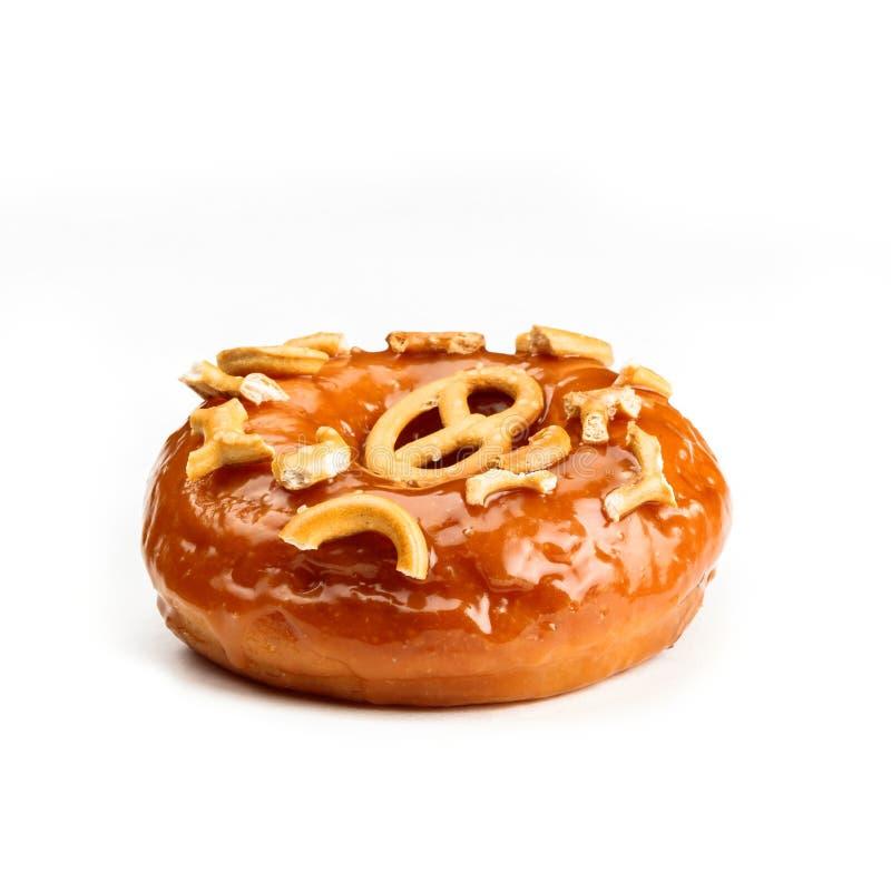 Filhós vitrificada com o caramelo e as partes de pretzel, isolados no fundo branco Vista do lado imagem de stock