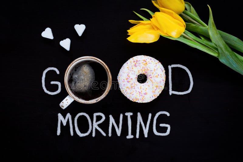 A filhós, xícara de café, coração deu forma a cubos do açúcar e a tulipas amarelas no fundo preto imagem de stock royalty free
