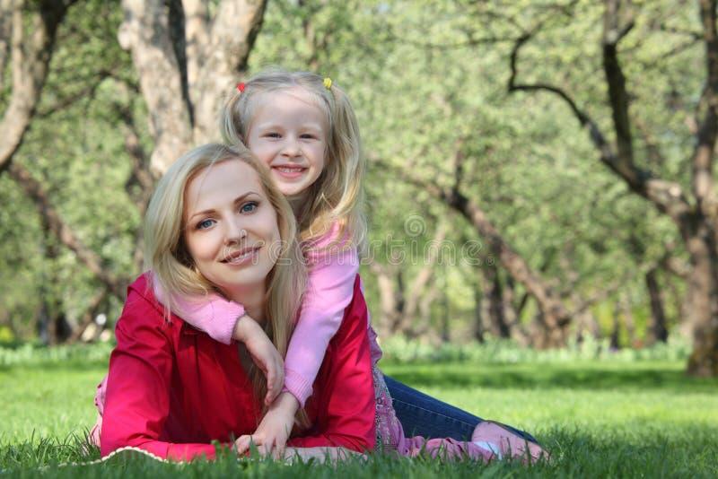 A filha abraça a matriz que encontra-se na grama foto de stock