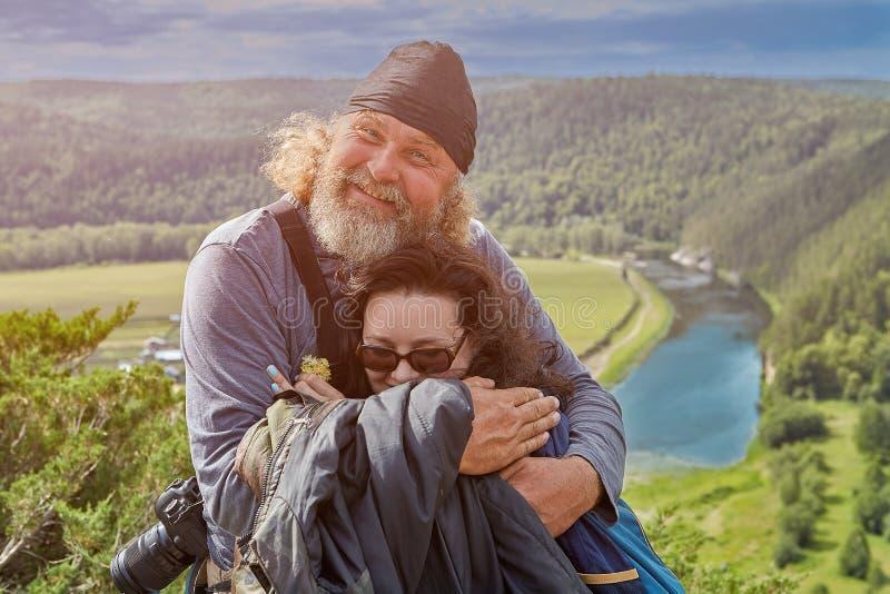 A filha abraça o pai sobre um penhasco imagens de stock royalty free