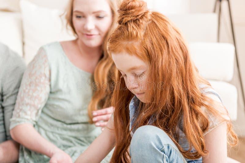 Filha adorável concentrada do ruivo com mãe atrás em casa imagem de stock royalty free