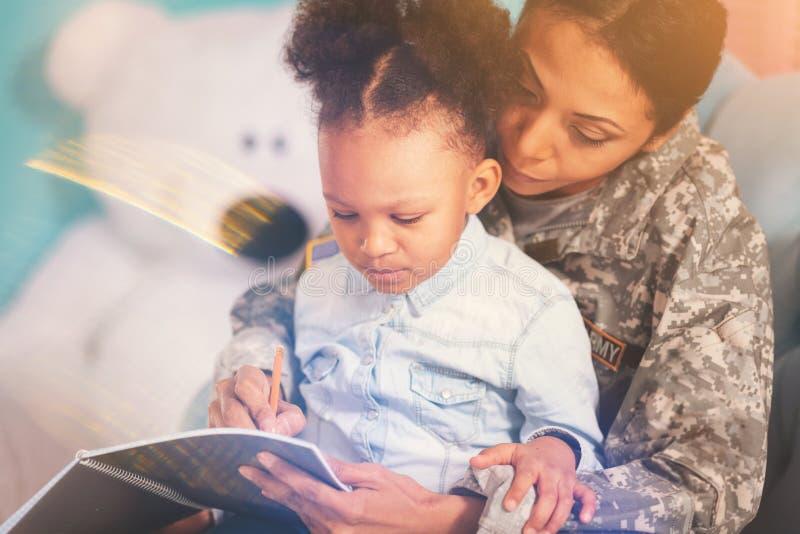 A filha adorável que olha sua mãe escreve no caderno fotos de stock royalty free