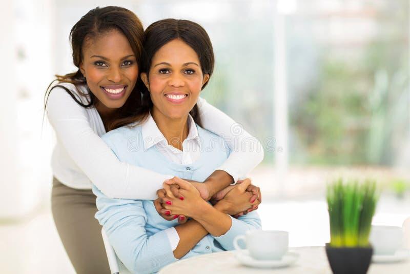 Filha africana que abraça a mãe fotos de stock royalty free