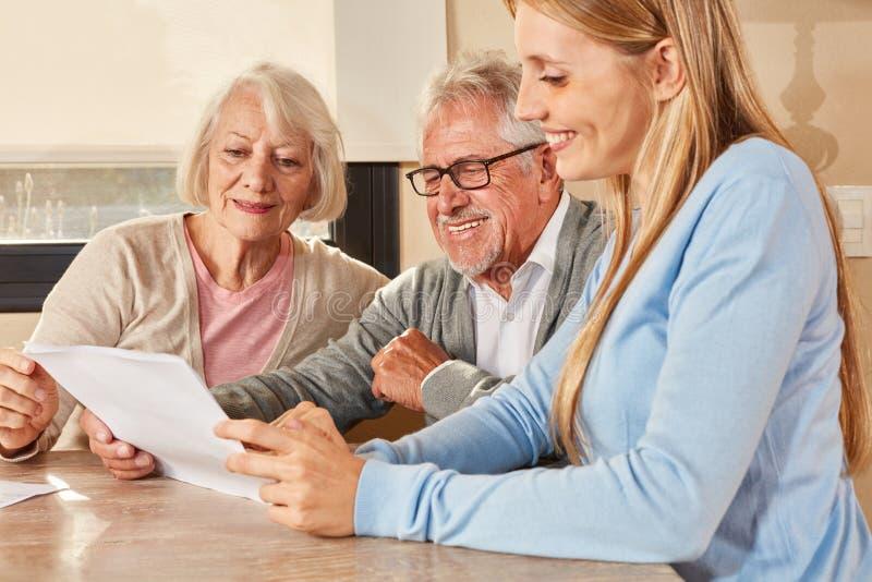 A filha ajuda as pessoas idosas com seguro e pensão fotografia de stock royalty free