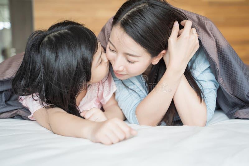 A filha beija o mordente da sua mãe e abraçando no quarto Fam?lia asi?tica feliz imagens de stock