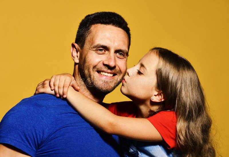 A filha beija seu paizinho no mordente Abraço da criança e do pai foto de stock