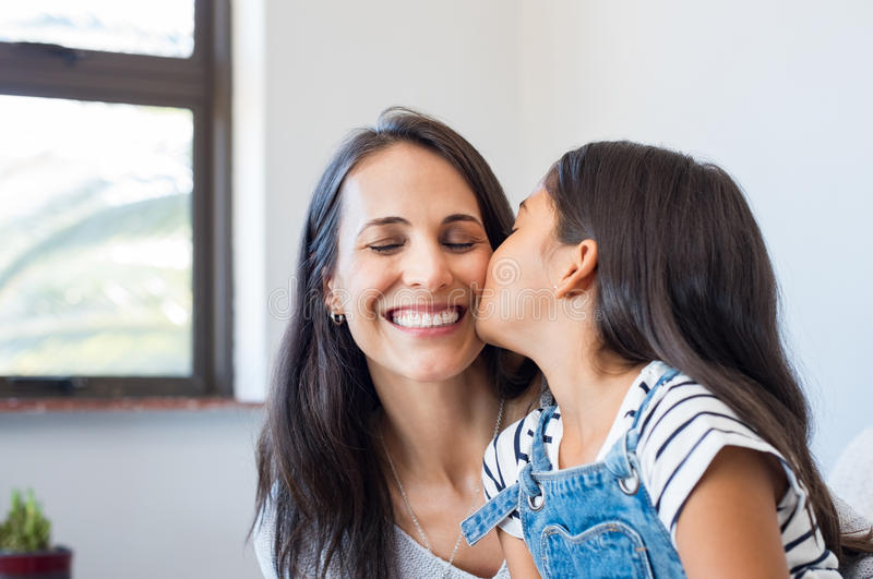 Filha bonita que beija a mãe fotos de stock