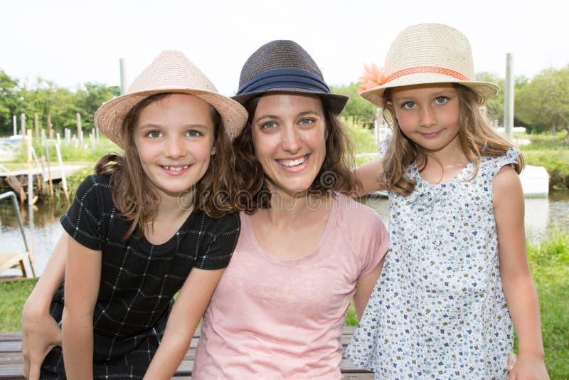Filha bonito da beleza no verão do chapéu de palha que levanta com mãe bonita imagem de stock