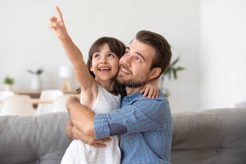 A filha bonito feliz mostra algo ao paizinho novo de sorriso fotos de stock