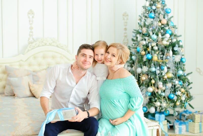 A filha caucasiano pequena que senta-se com pai feliz e a mãe grávida na cama próximo decorou a árvore de Natal fotos de stock royalty free
